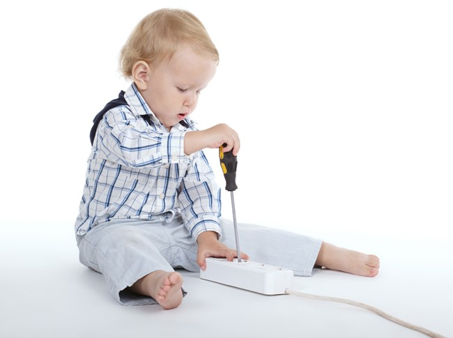 Child playing with an electrical device